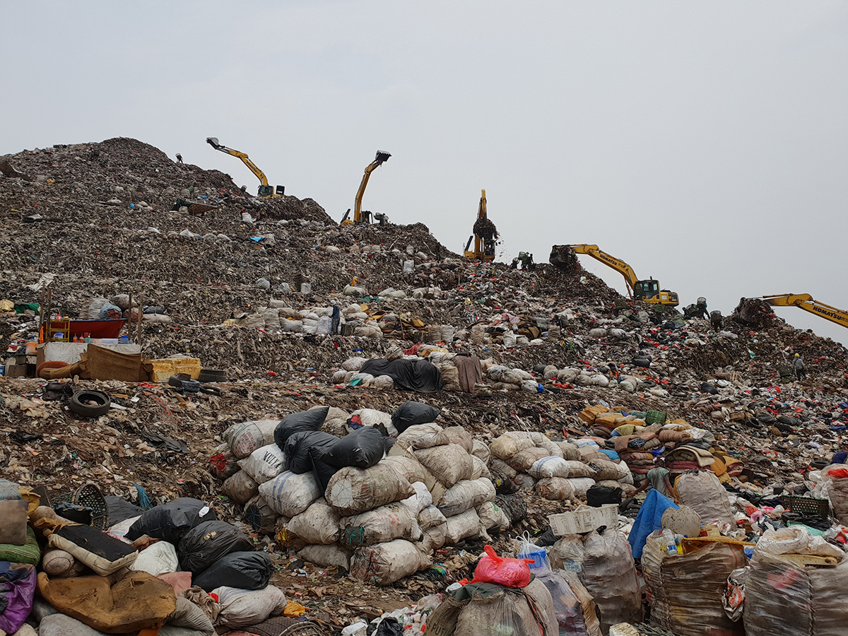 Gravemaskiner som rydder opp i en søppeldepot